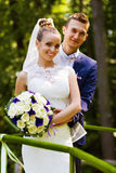 Groom and bride behind handrail. On nature royalty free stock photos