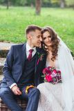 Groom bride with a bouquet hugging and sitting in park royalty free stock photo