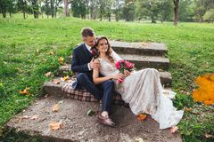 Groom bride with a bouquet hugging and sitting in park stock photos
