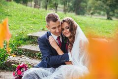 Groom bride with a bouquet hugging and sitting in park stock images