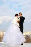 Groom and bride with bouquet of roses embrace Royalty Free Stock Photography