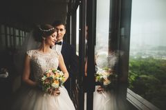 Groom and bride with a bouquet standing on terrace with green nature view stock images