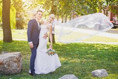 Groom, bride, bridal veil flying Royalty Free Stock Photography