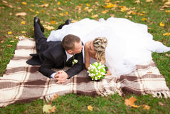Groom and bride and bride lying on plaid at park and kissing Royalty Free Stock Photo