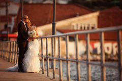 Groom and bride on a bridge near the sea Royalty Free Stock Photography