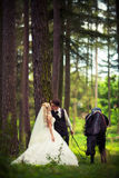 Groom with the bride and a brown horse Stock Photography
