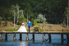 Groom with Bride and Champagne. Groom holding bride`s hand and champagne bottle on bridge Royalty Free Stock Images