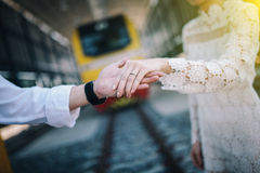 Groom and bride clasp hands. Couple , groom and bride wear wedding ring, clasp hands behind is train and railway at train station. Away so far for love is Royalty Free Stock Photo