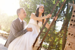 Groom and bride climbing a rusty ladder Royalty Free Stock Photo