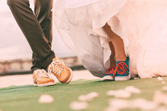 Groom and bride in colourful plimsolls on carpet Royalty Free Stock Images