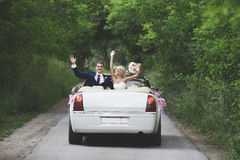 The groom and the bride in a convertible car royalty free stock photography