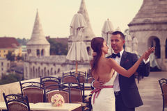 Groom and bride dancing in the city Stock Images