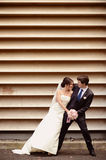Groom and bride dancing near a stripped wall Royalty Free Stock Photo
