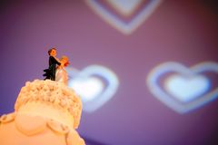 Dancing groom and bride dolls made from sugar on the top of wedding cake stock images