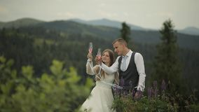 Groom with bride drink champagne on a mountain hills. Wedding couple. Family stock video
