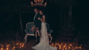 Groom and bride embrace and kiss at night, standing before couch in dark forest. stock video