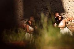 Groom and bride embracing near brick wall Royalty Free Stock Photos