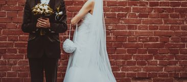 Groom and Bride embracing next to red brick wall. Stock Images