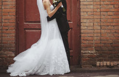 Groom and Bride embracing next to red brick wall. Royalty Free Stock Images