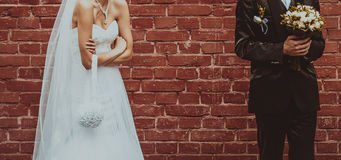 Groom and Bride embracing next to red brick wall. Stock Photos