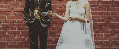 Groom and Bride embracing next to red brick wall. Royalty Free Stock Image