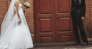 Groom and Bride embracing next to red brick wall. Royalty Free Stock Photos