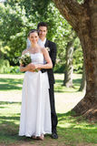 Groom and bride with flower bouquet in park Stock Photography