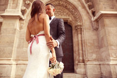 Groom and bride in front of a church Royalty Free Stock Photography