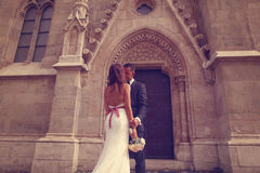 Groom and bride in front of a church Royalty Free Stock Photo