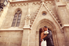 Groom and bride in front of a church Royalty Free Stock Image