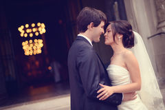 Groom and bride in front of the church Royalty Free Stock Photos