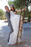 Groom and bride fun climbing a rusty ladder Stock Photography