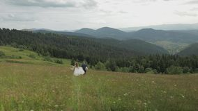 Groom with bride go for a picnic on a mountain hills. Wedding couple. Family stock footage