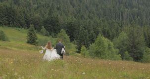 Groom with bride go for a picnic on a mountain hills. Wedding couple. Family stock photos