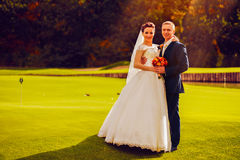 Groom and bride on golf field Royalty Free Stock Photo