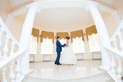 Groom and bride in hall with staircase Stock Images