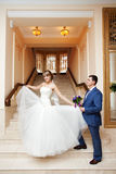 Groom and bride in hall with staircase Royalty Free Stock Photos