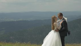 Groom with bride having fun on a mountain hills. Wedding couple hugging stock footage