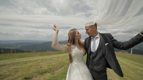 Groom with bride having fun on a mountain hills. Wedding couple under the veil. Happy family. Man and woman in love. Lovely groom stock video