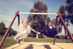 Groom and bride having fun on a swing set Stock Photo