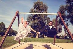 Groom and bride having fun on a swing set Stock Photo