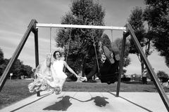 Groom and bride having fun on a swing set Stock Photos