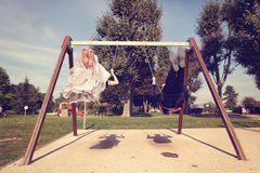 Groom and bride having fun on a swing set Royalty Free Stock Image