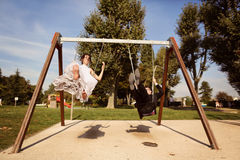 Groom and bride having fun on a swing set Royalty Free Stock Photos