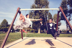 Groom and bride having fun on a swing set Stock Image