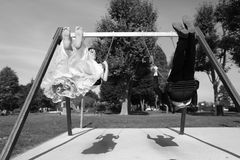 Groom and bride having fun on a swing set Royalty Free Stock Photography