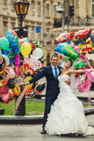 Groom and bride holding ballons on the background city Royalty Free Stock Images