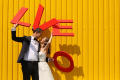 Groom and bride holding big LOVE letters Stock Images