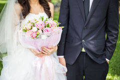 Groom and bride holding bouquet Stock Image