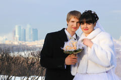 Groom and bride holding bouquet and look at camera Royalty Free Stock Image